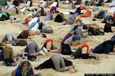 Australians protest climate inaction by burying heads in sand on Bondi Beach, November 13, 2014